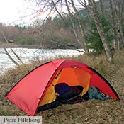 A red Unna on a river bank in Washington. One corner of the inner tent unhooked to create a virtual vestibule.
